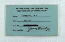 "Image of 2016.015.002.31 - Alyeska Pipeline Orientation Certificate of Completion Badge, August 4, 1975. This is a rectangular laminated blue paper badge issued to James C. Thompson for completing orientation training for the Trans-Alaska Pipeline construction project. Bold text at top center reads, ""ALYESKA PIPELINE ORIENTATION  /  CERTIFICATE OF COMPLETION.""  Below, information is typewritten on lines for name, date, social security number, and certificate approval. Text reads, ""Name: Thompson, J.C.  /  Date: 8/4/75  /  S. S. No. [crossed out in black ink]  /  Approved By: James Kisse[lli]ng."" The back side of the badge is blank."
