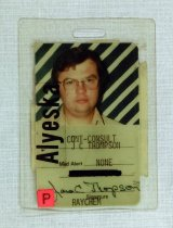"Image of 2016.015.002.32 - Alyeska Pipeline Service Company Identification Badge, 1975. This is a rectangular laminated Alyeska identification badge issued to James C. Thompson for the Trans-Alaska Pipeline construction project. A color photograph of Thompson against a green and white diagonal striped background fills the upper half of the badge. Thompson has medium length brown hair and wears a light colored collared shirt and wire rim glasses. The lower half of the badge shows printed lines with information typewritten in black ink. Text reads, ""CONT - CONSULT [construction consultant]  /  J C THOMPSON  /  Med Alert NONE  /  [Social Security number crossed out in black ink]  /  James C Thompson [cursive signature in blue ink]  /  Signature  /  RAYCHEM."" A large `P' in black ink on a square of pink paper is adhered to the bottom left corner, and a sticker with ""Alyeska"" in black ink on a clear plastic background is adhered vertically at center left over the photograph and printed information. There is a 0.125"" x 0.5"" hole at top center for attaching a strap. The back of the badge has a torn adhesive label with a white background and a black and red horizontal stripe at center. Partial text is visible. From top to bottom, ""A [black ink]  /  WOR[illegible, printed diagonally in red ink]  /  0 [illegible, red ink]  /  0 [illegible] 19  /  [illegible, black ink] S: OCT 3 [red ink]."" Thompson notes that the text on the back of the badge was likely entrance and exit stamps from the various construction camps working on the pipeline."
