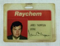 "Image of 2016.015.002.33 - Raychem Corporation Employee Badge, c. 1980s. This is a rectangular laminated identification badge issued to James C. Thompson. The ID consists of a white piece of paper with a 5/8"" red band across the top. The ""Raychem"" text logo appears in white font at top center on the red band. ""JAMES THOMPSON  /  20391"" is typewritten in black ink on the lower right side of the paper above a handwritten cursive signature ""James C Thompson,"" also in black ink. A 1.25"" x 1.25"" color photograph of Thompson is placed at bottom left. Thompson, who has short dark brown hair, appears from the shoulders up against a red background wearing a green plaid jacket over a white collared shirt. There is a 0.125"" x 0.5"" hole at top center for attaching a strap. The back side of the badge is blank."