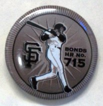 "Image of 2017.001.001 - Bonds HR No. 715 Button, 2006. This button is made of plastic and is on a parchment of paper with the insignia of the SF Giants as 2012 World Champions. This button is painted in dark gray with black circle in the middle. It has a round shell in the front. In the left middle of the black circle is the symbol of the San Francisco Giants with the ""S"" in San is interlocked with the ""F"" in Francisco. In the middle of the black circle is a silhouette of a dark skinned figure swinging a black bat with his hands and arms while in his white SF Giants uniform and black helmet. Toward the right of the middle of the black circle, painted in black and in bold, the text reads ""BONDS  /  HR No.  /  715"". The text ""715"" is larger than the text  ""BONDS  /  HR No."" above. At the back of the button, which is the pin-back, there is a copper spring pin in the middle of the back inside of the button's shell."