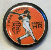 "Image of 2017.001.002 - I WAS THERE BONDS HR Button, 2007. This button is made of plastic and is on a parchment of paper with the insignia of the SF Giants as 2012 World Champions. This button is painted with a black outside border with a white circle inside. Inside the white circle, painted in orange, there is some black and bold painted text at the top corner that reads ""I WAS THERE"". The text ""I WAS"" and ""THERE"" are separated by part of the silhouette of the dark skinned figure's bat in his arms. In the left middle of the button, is the symbol of the San Francisco Giants with the ""S"" in San is interlocked with the ""F"" in Francisco. In the middle of the black circle is a silhouette of a dark skinned figure swinging a black bat with his hands and arms while in his white SF Giants uniform and black helmet. Toward the right of the middle of the black circle, painted in black and in bold, the text reads ""BONDS  /  HR"" with the text ""HR"" larger than the text ""BONDS"" above. At the back of the button, which is the pin-back, there is a copper spring pin in the middle of the back inside of the button's shell."