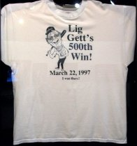 "Image of 2017.005.001 - Liggett 500th Win T-shirt, 1997.  White cotton and polyester T-shirt with dark blue cartoon image of Jim Liggett next to text that reads ""Lig  /  Gett's  /  500th  /  Win!  /  March 22, 1997  /  I was there!"" Figure is wearing a dark blue Carlmont baseball cap, glasses, white polo shirt with ""Scots"" on proper left side of chest, dark blue pants, and white lace-up shoes. He has a softball in his left hand and a bat in his right.  Hanes heavyweight 50/50 T-shirt is size adult XL (46-48)."