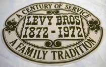 "Image of 1975.138.001 - Levy Brothers Centennial Banner, 1972. Cream felt background with green printed outer border with green bold painted text that reads ""A CENTURY OF SERVICE  /  A FAMILY TRADITION"". In center, inside rectangular border, isgreen bold painted text that reads ""LEVY BROS  /  1872-1972"". Has stylized fleur-de-lis on each side of the oval shaped banner. Text and pattern not visible on back."