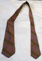 "Image of 1976.069.019 - Men's Necktie, n.d. Silk red and white checkered tie with alternating yellow and black rectangular stripes. On inside of tie are two tags, one black tag with green stitched text ""Loewe & 7 Wierlein  /  317 B Street  /  San Mateo, Calif."" The second tag is white with blue stitching ""All Silk  /  Hollyvogue  /  Made California""."