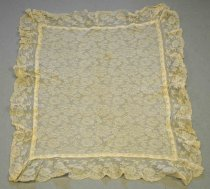 Image of 1981.073 - Lace Table Scarf, n.d. Rectangular shape, off white lace with floral pattern. Scalloped ruffle border of same color and material.