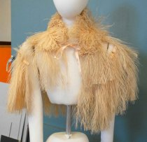Image of 1986.155 - Feather Capelet, n.d. Blush or champagne-colored feather capelet, designed to be worn wrapped around the shoulders. Three rows of feathers on blush-colored netting, also known as tulle. The feathers at the top or neck portion of the capelet are a different type than the bottom two rows of feathers, although the color matches exactly. The capelet has two rows of ribbon where the feather rows are attached to the tulle. The item appears to be hand-sewn. Two pieces of ribbon serve as the ties at the neck.