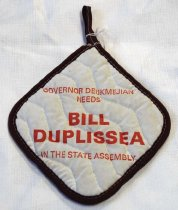 "Image of 1987.027.001 - Bill Duplissea Political Campaign Potholder, c. 1986-1988.  Used in political campaign by Bill Duplissea and Ed Bocciocco for Assembly office and given to women voters. Cotton off-white potholder with a burgundy outside hand sewn border. Square in shape. Attached on one side is a small burgundy cotton loop that is hand sewn to the top.  In the middle of the potholder, printed in red and in bold with small lettering, the text reads ""GOVERNOR DEUKMEJIAN  /  NEEDS"". Below the text above, printed in red and in bold with huge lettering, the text reads ""BILL DUPLISSEA"". Below the text above, printed in red and in bold with small lettering,. the text reads ""IN THE STATE ASSEMBLY"". On the back of the potholder, there is a colorful floral design with green, yellow and blue with red flowers with yellow branches in a white background on one side with a blue background with yellow and red flowers and white dots below, a red and white checkered spots to the right of the blue background. To the left of the blue background on the back, is a red background with yellow and green pattern with a black border with lines sticking out from it."