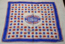 "Image of 1987.051 - Levy Bros Centennial Scarf, 1972.  Silk rayon blend scarf is white with blue and red print.  Center has an oval emblem that reads ""A CENTURY OF SERVICE  /  LEVY BROS  /  1972-1972  /  A FAMILY TRADITION.""  Border along outer edge consists of a 1 1/4"" blue band surrounded by a thin blue band and a thicker red band on either side.  White ground has stylized fleur-de-lis motif in alternating red and blue."