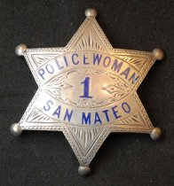 "Image of 1997.320.003 - Irene Farrell's San Mateo Police Badge, 1926. This police badge was presented to Irene Farrell, San Mateo's first Policewoman from T.F. Burke, Chief of Police. The badge is made of metal, and sterling silver. The badge is shaped like a star with round tips on the ends with a inside squiggly design surrounding the front of the badge, and a design of a thin lines across the inside of each side of the star. In the middle of the badge, at the top, painted in blue, the text reads ""POLICEWOMAN"". Below the text above, in the middle of a curved design, the text reads ""1"". Below the text above, in between two lines, the text reads ""SAN MATEO"". The text ""1"" is bigger than both of the text above. On the back of the badge, engraved and in bold, the text reads ""PRESENTED TO  /  IRENE  FARRELL  /  JUNE 26 - '26  /  BY  /  T.F. BURKE  /  CHIEF OF POLICE"". Below the text above, in tiny print, the engraved text reads ""STERLING"". Also on the back of the badge is a metal pin that is held together by a metal safety patch on the back."