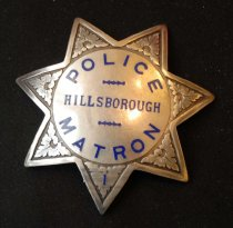 "Image of 1997.320.004 - Irene Farrell's Hillsborough Police Matron Badge, 1942 .  This silver metal badge belong to Irene Farrell of Hillsborough, the 1st Policewoman in San Mateo, CA. The badge is shaped like a star with floral motifs engraved on the badge near the end of each tips of the front of the badge. In the middle of the badge, in a circle, printed in blue and bold, the text reads ""POLICE  /  HILLSBOROUGH  /  MATRON"". The text ""HILLSBOROUGH"" is smaller than both of the text above with two small blue lines in between the text ""POLICE  /  HILLSBOROUGH"" and the text ""HILLSBOROUGH  /  MATRON"". On the back of the badge towards the bottom left, in tiny and bold lettering, the engraved text reads ""IRVINE & JACHENS  /  S.F."" On the back of the badge towards the bottom right, in tiny and bold lettering, the engraved text reads ""STERLING"".  Also on the back of the badge is a metal pin that is held together by a metal safety patch that looks like a small loop on the back."