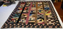 "Image of 1998.062.005 - Crazy Quilt, c. 1880.  Quilt is comprised of 30 8""x8"" 9-patch and crazy quilt blocks of various materials and colors.  On one block are embroidered the initials ""pHg.""  Blocks are divided by 2.5"" sashing on all sides except on the outer blocks along the longest outside edges.  Pieced edges are embroidered with various colors of feather stitching throughout.  Surrounding the blocks and sashing is a 6.5"" border comprised of printed pink roses with green leaves on a black ground.  This fabric has been folded over to the back to create the binding.  Backing is comprised of two pieces of red fabric, a medium and dark red, with the seam extending down the center of the length of the fabric.  Back of feather stitching is only visible around the inner edge of the outside border.  Inner layer of fabric is white cotton."