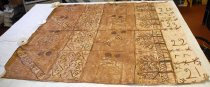 "Image of 2003.074.002 - Tapa Cloth, n.d.  Natural fiber blanket comprised of large sections of plant material that has been soaked in liquid (water?) and pounded together.  Light tan colored ground has been painted light brown in sections and has dark brown writing.  Dark brown lines divide the piece into 20 squares or blocks divided into five columns of four blocks each.  The first column of 19""x19"" squares are painted brown with alternating light colored diagonal lines or circles on every other block.  Diagonal lines appear to have capital letters: ""VAHAAKOLO"" and circles have a leaf and plus-sign motif.  At the top of all four blocks are two dark brown circles approximately 2.5"" in diameter.  The second column is lighter in color and is comprised of 12"" x 19"" blocks with dark brown line drawings inside that include plus-signs, x's, stars, circles, squares, diamonds and zigzags.  While all four are similar, the design varies slightly in each one.  The third column has large 19"" x 19"" blocks with the two 2.5"" diameter dark brown circles at the top similar to the first column.  Each of these blocks has a line drawing in the center, possibly of animals.  The fourth column has 14"" x 19"" lighter colored brown blocks with two trees and a fence (? two parallel lines with a row of x's between them) on each block.  The trees' bases are against column 5.  The fifth column is comprised of unpainted 11"" x 19"" blocks with the numbers ""21"", ""23"", ""22"" and ""21"" written on each one from top to bottom.  Numbers are separated with a single horizontal line overlaid with x's that looks similar to barbed wire."