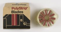 "Image of 2016.015.002.44 - Raychem PolyStrip Blade Dispensers, c. 1960s-1970s. This is a cardboard box of five Raychem Corporation PolyStrip replacement blade packs (A-E). The red plastic polyarylene blades were manufactured for use with a PolyStrip wire stripper device. The blade packs are circular containers with rounded tabs on each side that hold up to ten 1"" x 0.25"" blades in a radiating fashion.  They are made from clear plastic that has ""PolyStrip  /  Raychem AT6500"" and ""Replacement Blade Pack"" molded into the surface. Each blade in the pack has ""Raychem"" and ""Pat.  /  Pend"" molded into the top side. The tan cardboard box (F) has a flip top with tabs for securing the lid. The top of the lid shows a red and black graphic of a PolyStrip wire stripper with ""PolyStrip™  /  Blades"" printed in red and black font at top center. ""Raychem"" is printed on the front and back sides of the box and ""5 ea. PolyStrip™  /  Blade Dispensers  /  No. 959003"" is printed on right and left sides.
