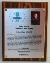 "Image of 2017.010.002 - Earl Hansen Sports Hall of Fame Plaque, 2017.  Rectangular brushed metal plaque attached to laminate wood grain board with copper colored brads.  Hole drilled in top center of wood portion. Peninsula Sports logo in upper left corner of metal portion - green trophy cup surrounded by blue stars - ""2017 Peninsula Sports Hall of Fame."" 