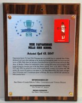 "Image of 2017.010.006 - Nick Pappageorge Sports Hall of Fame Plaque, 2017. Rectangular brushed metal plaque attached to laminate wood grain board with copper colored brads.  Hole drilled in top center of wood portion. Peninsula Sports logo in upper left corner of metal portion - green trophy cup surrounded by blue stars - ""2017 Peninsula Sports Hall of Fame."" 