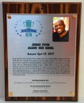 """Image of 2017.010.007 - Jimmie Pryor Sports Hall of Fame Plaque, 2017. Rectangular brushed metal plaque attached to laminate wood grain board with copper colored brads.  Hole drilled in top center of wood portion. Peninsula Sports logo in upper left corner of metal portion - green trophy cup surrounded by blue stars - """"2017 Peninsula Sports Hall of Fame.""""    Photo of Jimmie Pryor in upper right corner of metal inset. Blurred colorful background. Black smiling man, bald with goatee, wearing black v-neck t-shirt.   Text under logo and photo reads """"Jimmie Pryor  /  Aragon High School  /  Inducted April 13, 2017  /  It was obvious when Jimmie Pryor walked onto the Aragon High Campus in the late  /  1980s: He was a natural. And, perhaps, it was not really a surprise. A member of a family  /  blessed with a number of outstanding athletes, Jimmie became a multi-sport star in short  /  order. He was All-Peninsula Athletic League, All-San Mateo County and, eventually,  /  All-State in both football and basketball. As a senior, he was named State Athlete of the  /  Year. He also was selected to play football in the North-South Shrine Game and in a  /  state basketball all-star game. Capping off a brilliant senior season, he won the high jump  /  event in the Central Coast Section track and field meet. He later played football at the  /  University of Utah."""" (Name and school bold text, all caps, induction date bold cursive, biography case sensitive)   Sponsorship information below biography.  Text included in inscription field."""