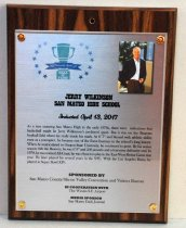 """Image of 2017.010.009 - Jerry Wilkinson Sports Hall of Fame Plaque, 2017. Rectangular brushed metal plaque attached to laminate wood grain board with copper colored brads.  Hole drilled in top center of wood portion. Peninsula Sports logo in upper left corner of metal portion - green trophy cup surrounded by blue stars - """"2017 Peninsula Sports Hall of Fame.""""    Photo of Jerry Wilkinson in upper right corner of metal inset. Outdoors background, white male, gray hair, receding hairline, wearing light blue button down shirt (open at collar), navy sports jacket and brown pants.   Text under logo and photo reads """"Jerry Wilkinson  /  San Mateo High School  /  Inducted April 13, 2017  /  As a teen entering San Mateo High in the early 1970s, there were indications that  /  basketball might be Jerry Wilkinson's preferred sport. But it was on the Bearcats  /  football field where he really made his mark. At 6'7"""" and blessed with athletic ability  /  even as a youngster, he became one of the finest linemen in the school's long history.  /  When he matriculated to Oregon State University, he continued to grow. By his senior  /  season with the Beavers, he was 6'9"""" and 250 pounds and a fearsome defensive end. In  /  1978, he was named All-Coast; he was chosen to play in the East-West Shrine Game that  /  year. He later played for several years in the NFL. With the Los Angeles Rams, he  /  played in Super Bowl XIV.""""(Name and school bold text, all caps, induction date bold cursive, biography case sensitive)     Sponsorship information below biography.  Text included in inscription field."""