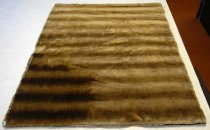 Image of 1968.070.001 - Carriage Robe, c. 1900.  Synthetic fiber carriage robe is made to look like fur.  It is comprised of two pieces of fabric sewn together along outer edge.  One side is a light gold color with brown stripes going through it; the other is solid black.  Used to keep laps warm during carriage rides.