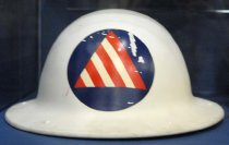 "Image of 1971.226.001 - Civilian Defense Air Raid Warden Helmet, c. 1942-1945. This metal helmet is round in shape and is painted in white. In front of the top center portion of the helmet's head, there is a blue circle with a red/white striped triangle, which is the symbol for Civil Defense Air Raid Warden. At the back of the helmet, there are bolts painted in white that connect to the helmet's head and chinstrap adjustments and are spread out on each corner of the metal helmet.  Inside the middle of the helmet, the white painted bolts are connected to metal brackets that are slightly bent, in which connects to a head adjustment made of leather that covers the head. The leather head adjustment is next to and parallel to the straps of white fabric which is tied to a circle made of black fabric. The middle straps of the white fabric are tied to a brown chinstrap with a metal loop bracket adjustment for the chin with a metal nail holding the strap. The chinstrap also has a metal black circle on each end that connects it to the slightly bent metal brackets on each left and right end of the metal helmet.  At the bottom front portion of the back of the metal helmet, engraved in white and bold, the text reads ""...No  217714  /  No  D113432..."". At the bottom portion of the back of the metal helmet, engraved in white and bold, the text reads ""...MCDONALD CO  /  LOS ANGELES""."