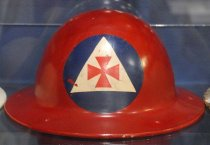 "Image of 1971.226.003 - Civil Defense Auxiliary Fireman Helmet, c. 1942-1945. This metal helmet is round in shape and is painted in red. In front of the top center portion of the helmet's head, there is a blue circle with a white triangle with a red cross in the middle, which is the symbol for Civil Defense Auxiliary Fireman. At the bottom portion of the helmet, there are bolts painted in white that connect to the helmet's head and chinstrap adjustments and are spread out on each corner of the metal helmet.  Inside the middle of the helmet, the white painted bolts are connected to metal brackets that are slightly bent, in which connects to a head adjustment made of leather that covers the head. The leather head adjustment is next to and parallel to the straps of white fabric which is tied to a circle made of black fabric. The middle straps of the white fabric are tied to a brown chinstrap with a metal loop bracket adjustment for the chin with a metal nail holding the strap . The chinstrap also has a metal black circle on each end that connects it to the slightly bent metal brackets on each left and right end of the metal helmet. At the bottom front portion of the back of the metal helmet, engraved in white and bold, the text reads ""PATENT...  /  No  217714  /  No  D113432..."". At the bottom portion of the back of the metal helmet, engraved in white and bold, the text reads ""...MCDONALD CO  /  LOS ANGELES""."