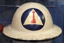 "Image of 1971.226.004 - Civilian Defense Road Repair Unit Helmet, c. 1942-1945. This metal is round in shape and in gray. In front center of the helmet's head, there is a blue circle with a white triangle with a symbol of a red shovel in the middle, which is the insignia for Civil Defense Road Repair Unit. On the back of the helmet on the outside border, it is surrounded by metal bracket ends with each of them are tied to a brown cloth strap, which is connected to a black fabric circle in the middle, and a metal nail in each one holding each individual strap together. Surrounding in the middle, above the black fabric circle, is a brown leather head strap, which covers the portion of the head in the helmet. On the left and right metal ends of the helmet, the brown cloth straps are connected to a brown small leather chinstrap with a small metal loop bracket used for adjusting the strap on to the chin. In the middle of the inside of the helmet, in a red circle with a single white star, the painted text in blue says ""Mfd. by  /  LOS ANGELES"".  The words ""LOS ANGELES"" are in bold. In between the red circle, in white outer border with a blue background, in white, the painted text says ""B.F. McDonald CO."" The words ""McDonald"" is disproportionately bigger than the rest of the text above."