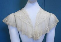 Image of 1984.137.001 - Lace Collar, c. 1910-1940. Off-white tulle netting with floral design on the neckline. Tulle netting border with appliqué border and scalloped edging on the border. Chain-like edging on the upper portion of the neckline. Machine made.