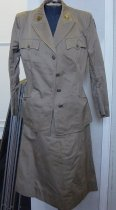 "Image of 1999.068a - Woman's Army Corp (WAC) Jacket, November 2, 1942. This jacket is in khaki brown, and is made of cloth. The jacket has a collar with two gold lapel pins on each end of the sleeve. Both gold lapel pins are round in shape and pinned to the collar by brass round pins. The one on the left end of the collar has an image of Athena, goddess of wisdom, craft and war, which is the insignia for the Women's Army Corp (WAC). On the one on the right end of the collar, embossed in gold, and in bold, the text reads ""U.S."". The jacket has two pockets near the top portion of the chest of the jacket with brown, small round buttons that are embossed with the symbol of a bald eagle. In the middle of the jacket, there are small holes on one end, and medium sized round buttons, shaped similar to the small round buttons on the the pockets at the top. The buttons fit nicely through the small holes on the one end. Each of the buttons are embossed with same symbol of the bald eagle. Towards the bottom front of the jacket, there are two pockets, one on each side, stitched a little bit on the outside border of the pocket. Inside the right hand pocket, printed on a white piece of cloth, the text reads ""JACKETS, WAAC, MEMBERS,  /  SUMMER  /  SIZE 18R  /  GAYNES INC  /  Cont. W-669 QM 22623  /  Dated Nov. 2  1942  /  Spec. No.  Tent. Spec.  /  P.Q.D.  No. 216A  /  Dated August 29, 1942, Type 1  /  Stock No. 55-J-550-58  /  Phila M.Q. Depot  /  Inspector"". The text ""JACKETS, WAAC, MEMBERS""  and ""Dated August 29, 1942, Type 1"" are disproportionately smaller than the text above and in bold. The text ""SIZE 18R  /  GAYNES INC"" is disproportionately bigger than the rest of the text and is in bold. In between the text above and the word ""Inspector"", there is a signature in ink with two lines at the top and one line at the bottom of the signature. The jacket is stitched along the sides, front and back and on its sleeves. The jacket also has two sleeves with one of them at the top left shoulder has a blue round fabric badge with two gold wings surrounding a white star and a red circle in the middle. The blue round badge is stitched to the top left shoulder. At the bottom of the right sleeve, stitched to the sleeve, a black round badge with one ""S"" and one ""C"". The ""C"" is in the middle of the ""S"", making the two letters interlock. At the top right of the inside of the collar, printed on a white piece of cloth in black, the text reads "" SIZE  / 18R"". The words ""18R"" is disproportionately bigger than the text above."