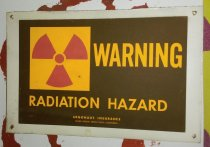 """Image of 2016.026.005 - Radiation Safety Sign, c. 1957-1999. Radiation safety sign used in an electron beam facility at the Raychem Corporation and later Tyco Electronics (Raychem was purchased by Tyco International in 1999). The sign was installed in the """"Beam One"""" area, which continued to be in operation through 2016. The rectangular metal sign has a white outer border with a brown background. A red trefoil radiation symbol is printed in a yellow square at upper left. Yellow text at upper right reads, """"WARNING,"""" and text at bottom center reads, """"RADIATION HAZARD."""" Small text at bottom center reads, """"ARGONAUT INSURANCE  /  HOME OFFICE: MENLO PARK, CALIFORNIA."""" Holes are punched at each corner of the sign for hanging."""