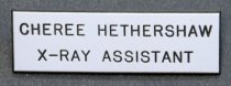 "Image of 2017.011.002 - Mills Memorial Hospital X-Ray Assistant Badge, c. 1964-1971.  White rectangular plastic badge with a black plastic inner layer.  Top of badge is inscribed with, ""CHEREE HETHERSHAW  /  X-RAY ASSISTANT"" so that black lettering shows through.  Onto back is glued a silver-colored metal pin for affixing badge to clothing."