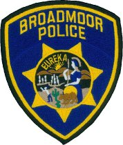 "Image of 2017.014.002 - Broadmoor Police Patch, n.d. This badge is black with a gold inside border around the badge with some gold bold text at the top middle that reads ""BROADMOOR POLICE"". In the middle of the badge is a gold star with a circle in the middle. The circle has a black background and shows a woman wearing a helmet and a staff with mountains below a yellow sun, a desert and a brown bear in the background. On the top corner of the black background, there is some small bold, and gold text that reads ""EUREKA"". This circle appears to be a symbol of the California seal."