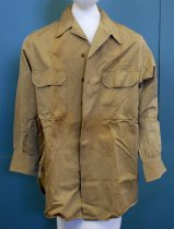 """Image of 2017.015.024C - WWII Army Uniform Long-sleeved Shirt of Joseph Dutilh, c. 1941-1945.  WWII Army Shirt of Joseph Dutilh, c. 1941-1945.  Khaki cotton long-sleeved dress shirt has two chest pockets with flaps, six tan buttons down the front and buttons at the cuffs. Along the top of the inside of the collar, printed in black ink and in bold, the text reads """"15-32"""". Printed in black above part of the collar, the text reads """"227"""". Directly below the text above, printed in black, the text reads """"727""""."""