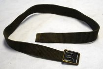 """Image of 2017.015.025 - Belt, 1961.  Short olive green belt with gold and black metal fasteners attached on each end. On one end of the belt on the back, printed in black and bold, the text  """"U.S.  J.C.H.D  1961"""". Towards the end of the text """"U.S.  J.C.H.D  1961"""", on one side behind the metal fastener, printed in black and bold, the text reads """"36""""."""