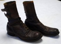 """Image of 2017.015.026A-B - WWII Army Uniform Boots (A-B) of Joseph Dutilh, c. 1941-1945.  Long brown leather shoes with two metal belt fasteners at the top, brown shoelaces in between metal holes in the middle and a nice curved edge heel with a small design of holes at the top of the shoe. On the bottom are several metal nails holding the heel around the top and end of the bottom of the heel. Embossed in bold and print on the back of the bottom of the heel on both shoes, the text reads """"U.S. ARMY"""". In the middle of the bottom of the heel on the left shoe, engraved in bold, the text reads """"U.S. NO 109   /   1/2 C"""". In the middle of the bottom of the heel on the right shoe, engraved in bold, the text reads """"U.S. No 199  /  1/2 C""""."""