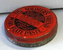 """Image of 2017.015.030 - The Soldiers Friend Pearl Plate Paste, c. 1941-1945. Small round container of metal polish with a red tin cover. At the top, in the inside circle, in black and bold printed text, the text reads """"THE SOLDIER'S FRIEND"""". Directly below on the same inner line on the inside circle, in black and bold text, the text reads """"PEARL PLATE PASTE"""". In between both of the text, is a small design consists of a small circle with four tiny spaced out and surrounding the small circle. In the middle of the circle, in a black background with red bold text , the text reads """"FOR  /  POLISHING THE  /  METALLIC PARTS OF  /  A SOLDIERS CLOTHING  /  AND EQUIPMENT"""". Directly below the text above, in a red background with black text with medium lettering, the text reads """"RUB THE PASTE WELL  /  ON WITH DAMP SPONGE  /  OR FINGER  AND POLISH  /  WITH BRASS BRUSH"""". Directly below the text above, in a black background with red cursive text, the text reads """"Considyne  /  Curtis & Co.  /  Bristol"""". At the bottom side of the tin, in black, and bold with medium lettering, the text reads """"MADE IN ENGLAND"""". On the back of the end cover, in black with fancy lettering, around the top, the text reads """"THE ORIGINAL SOLDIER'S FRIEND"""". The text """"ORIGINAL"""" is underlined. Directly below the text above, is a block of text in black and bold that reads """"For Polishing  /  the metallic parts  /  of a Soldier's Clothing  /  and Equipment"""". Directly under the text, is a line break design that consists of two lines with two ends end in a """"Y"""" shape surrounding a small circle. Underneath the line design break, is some more block of black text that reads """"Rub the Paste well on  /  with damp sponge or  /  finger and polish  /  with brass brush"""". There are little dots in front of each word in front or end on all four lines. Underneath the text above, in small and black lettering, the text reads """"Free from Acid""""."""