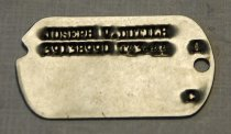 "Image of 2017.015.28A - WWII Army Dog Tag of Joseph Dutilh, c. 1941-1945.  Metal military dog tag is round in shape with a slight curve on one end and a hole on the other end. There is small stamped text at the top of the tag which both say ""JOSEPH V. DUTILH  /  39138990 T43-44"". On the side of each dog tag in between the metal hole on each side, the text reads ""A  /  C""."