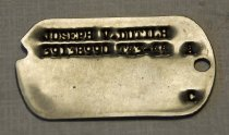 """Image of 2017.015.28B - WWII Army Dog Tag of Joseph Dutilh, c. 1941-1945.  Metal military dog tag is round in shape with a slight curve on one end and a hole on the other end. There is small engraved text at the top of the tag which both say """"JOSEPH V. DUTILH  /  39138990 T43-44"""". On the side of each dog tag in between the metal hole on each side, the text reads """"A  /  C""""."""