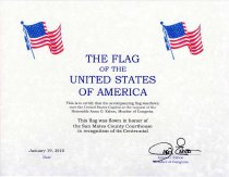 "Image of 2017.047.002 - United States Flag Certificate, 2010.  Paper certificate in a blue folder.  Folder has a gold U.S. House of Representatives stamp in the center.  Paper certificate is printed on parchment paper and affixed to folder benath mylar via cloth corner tabs.  There are images of American flags in the top corners.  ""THE FLAG of the UNITED STATES OF AMERICA"" is printed in blue.  Certificate goes on to state that ""This is to certify that the accompanying flag was flown over the United States Capitol at the request of the Honorable Anna G. Eshoo, Member of Congress.  This flag was flown in honor of the San Mateo County Courthouse in recognition of its Centennial."""