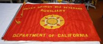 """Image of 2017.049.001 - USWVA Flag. Red and gold satin flag (a), with pole (b), and pole extension (c). Flag (a) is mostly red in the front and completely yellow on the back. On the front, written at the top of the flag in gold lettering, """"Unite Spanish War Veterans  /  Auxiliary."""" On the bottom is written, """" Department of California,"""" also in gold lettering. In the middle of the flag is a round, gold emblem. Along the outer edges there are black leaves stitched into the fabric to create an image of a gold wreath. In the middle is a white cross with eight red triangles, outlined in gold, extending out from the edges. In the middle of the cross is another emblem; this one, outlined in gold, has a blue ring with the words """"National  /  Auxiliary  /  U.S.W.V."""" written in gold lettering. On the inside of the emblem is a crudely stitched image with three figures standing on a shore. The figure on the left is dressed in a military uniform with a tall, wide-brimmed hat and is holding a rifle in both hands. The figure in the  middle is kneeling with his arms extended out to touch the side of the figure on the left and hold the hand of the figure on the right. The figure on the right is wearing sailor uniform with a flat hat with his right arm down to his side. The pole (b) is inside the left side of the flag. Protruding from the top is a spear-like end with a gold patina and gold rope and tassels tied around it. The pole extension (c) is aluminum. There is a small sticker on the metal that says in very faded lettering """"Hortie-Van  /  1926   MFG. Co  /  PA...A, CA   91107."""""""