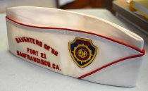 """Image of 2017.049.002D - Daughters of '98 Garrison Cap, c. 1925-1990. Red and white cloth garrison cap. The top seams of along the folded flaps are stitched in red thread. Along the right side, """"DAUGHTERS OF '98  /  FORT 21  /  SANFRANCISCO, CA."""" is sewn in red thread. Next to it, towards the front of the cap, is a blue shield-shaped patch with gold stitched borders. Stitched, in red, at the top of the patch is """"D OF '98."""" Below this is a gold stitched insignia with the design/shape of a compass. Inside, stitched in a circle in red, is """"NATIONAL  AUXILIARY  /  USWV."""" In the middle of the patch is another stitched, gold circle with three figures on the inside.  The figure on the left is standing and holding a rifle; they may be wearing a hat. The figure in the middle is kneeling towards the figure on the left with their arm stretched out towards the left figure. The figure on the right is standing with their hands on their hips. The lining on the inside is white and has a satin-like shine. A white tag on the inner band reads """"H  /  W          515664  /  7 1/2."""" There is a logo at the top and in the middle of the tag but its is difficult to discern details."""