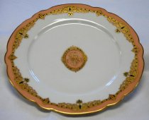 """Image of 1972.090.002 - Ralston Lunch Plate, 1867.  White porcelain china lunch plate has a gold painted scalloped rim.  Outer edge just inside rim is coral in color.  Below the coral is a band of gold interspersed with green squares, gold scroll work and gold and green crown shapes.  A gold """"R"""" monogram is in the center on a coral-colored ground inside an oval of the same gold and green banding."""