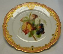 "Image of 1972.090.015 - Ralston Dessert Plate, 1867.  White porcelain china plate has a recessed flat 6"" center with a slightly flared rim that has scalloped edging.  Center is painted with an image of a blackberry vine and a white butterfly sitting on a ripe blackberry.  Leaves on bush are beginning to turn red.  Rim is coral in color bordered by gold.  Inner gold band is very decorative.  It is interspersed with  green circles, Fleur-de-lis, scrollwork, and grown shapes.  Interrupting band at top center is an oval of the same pattern in the center of which is the letter ""R."""