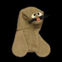 """Image of 2016.024.001 - Ray the Raychem Seal Hand Puppet, c. 1974-1975. Promotional Ray the Raychem Seal hand puppet made by the Puppet Factory for the Raychem Corporation. The puppet has brown faux fur, white and black felt eyes, orange pom-pom nose, and black yarn whiskers. The mouth is lined with pink felt, and two flippers hang at either side of the body. A label sewn inside the body reads, """"THE PUPPET FACTORY  /  ALL NEW MATERIALS."""""""