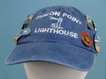 "Image of 2017.008.067A.1 - Pigeon Point Cap. Blue cotton baseball cap with a light brown leather adjustable strap with a metal flip closure. The loose strap is tucked into a pocket built into the edge of the cap. On the front crown, there is a white embroidered image of a lighthouse with the words ""PIGEON POINT  /  LIGHTHOUSE"" sewn above and below. On the back ""PESCADERO, CA"" is embroidered. Twenty-one different pins decorate the cap; they are pins representing: San Francisco Maritime National Historical Park, California State Park Volunteer 100 hours, Piedras Blancas Light Station Bureau of Land Management , City of Avalon Catalina Island, Point Reyes National Seashore , California State Parks Volunteer, Junior Ranger, Hearst Castle, CA State Park Volunteer Appreciation, Santa Barbara, Vancouver Island, Spring Point Lighthouse, The Unite States Lighthouse Society, Point Bonita, Assistant Keeper at Pigeon Point Lighthouse, and U.S.L.H.S Efficiency."