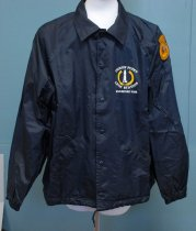 "Image of 2017.008.067B.3 - Pigeon Point Jacket. Large nylon navy blue windbreaker with navy blue snap buttons down the front, two hand pockets, adjustable strings, and a white cotton lining. On the front, left chest is a white illustration of a lighthouse surrounded by a large gold laurel wreath; ""PIGEON POINT  /  LIGHT STATION  /  STATE HISTORIC PARK"" is printed in white above and below the lighthouse logo. On the back of the jacket is a larger version of the logo that covers the majority of the back with the same inscription. Sewn on the upper left hand shoulder is a gold and brown patch shaped somewhat like a kettle ball. On the top of the patch, embroidered in brown, is ""VOLUNTEER."" Inside the round portion of the patch is a brown embroidered bear; both above and below the bear is the inscription ""CALIFORNIA  /  STATE PARKS."""