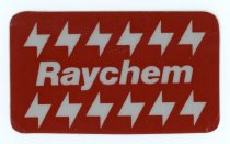 """Image of 2017.009.006 - Raychem Corporation Reflective Sticker, c. 1970s-1990s. Promotional reflective adhesive sticker produced by the Raychem Corporation. The 2"""" x 3.375"""" sticker is rectangular with rounded corners and has a split paper backing. """"Raychem"""" appears at center with a row of stylized electrical bolts above and below. The base of the sticker is made from gray reflective material and the red background is printed on top to create graphics and text."""