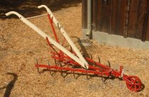 Image of RF2003.082 - Fourteen-tooth International Harvester reversible cultivator.  Red metal bosy has a wheel in front at the point of three bars that form a triangle with an upright lever at back center.  14 serpentine spikes are affixed vertically to metal bars.  Two off-white wooden handles extend out from center bar.  A wooden dowel and metal rod stretches between the handles just below the tapered and curved grips.