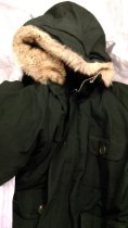 """Image of 2016.015.002.10 - Alyeska Arctic Wear Parka, c. 1972-1975. Down parka designed and produced by the Woolrich Company for the Trans-Alaska Pipeline construction project. The outer shell is constructed with dark green heat and flame resistant nomex aramid fiber. The hood is trimmed with tawny coyote fur, and two cotton cords can be pulled to cinch the hood into a tunnel shape for protection against wind. The front of the parka has four flap patch pockets. Each pocket is secured with a single round green button. The lower pockets are 10.75"""" x 9"""" and the upper pockets are slightly smaller at 7.75"""" x 6.25"""". The proper left top pocket also has a vertical button hole visible underneath the flap. A placket with five buttons covers a two way zipper closure. The top zipper slider has a brown leather pull attached. Olive green ribbed cuffs are sewn inside the sleeves and a rectangular brown leather patch is sewn on each elbow. Inside the parka, blue nylon lining is quilted over down insulation. A white and black rectangular label is sewn into the lining on the area of the upper back. A woven black border surrounds woven black text that reads, """"ALYESKA  /  ARCTIC WEAR."""" Two small tags are sewn underneath this label. A size tag is attached at bottom center marked """"L"""", and a tag sewn in a loop at the top right corner reads, """"OUTER-SHELL-NOMEX ARAMID FIBER  /  LINING-100% Nylon  /  INSULATION-Down."""" There are two 8"""" x 6.5"""" interior pockets near the waistline with elastic at the top opening. A white rectangular plasticized label used for writing someone's name into the coat is sewn on the proper left interior pocket. A cotton cord is sewn into the coat to cinch the waist, and a strap with two metal rings is sewn onto the back of the parka to secure the hood down. This coat was issued to Jim Thompson after he completed safety training for the Trans-Alaska Pipeline construction project in 1975. He notes that the jacket was one piece of a set of issued clothing, including a se"""