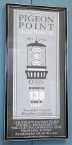 """Image of 2017.008.008 - Framed Pigeon Point Lighthouse Anniversary Poster, 2002. Narrow, tall framed poster commemorating Pigeon Point Lighthouse's 130th Anniversary. Poster is black, white, and light gray. At the top is printed """"PIGEON POINT LIGHTHOUSE"""" in black and white on a gray background. Below it is a stylized drawing of the lighthouse beacon, with the dates 1872 and 2002 on either side of its spire, and the California State Parks seal below it. Below that is written """"CELEBRATING 130 YEARS OF LIGHT,"""" the date, and location in black and white. This entire portion is surrounded by a striped white border. Around it is a black border that extends to the edge of the poster, with some tourist information printed in white at the very bottom on this black border. The frame is black with silver lines around the inside and outside edges. The back has a horizontal wire for hanging."""