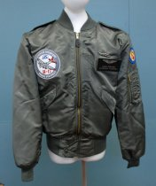 Image of 2017.008.030.2 - Moffett Field B-17 Jacket, 2006. Green nylon flight jacket. The material has a satin finish. Cuffs, collar, and the bottom of the jacket are made of an elastic polyester material. The jacket has two shoulder straps extending from the top of the sleeve to button near the collar. Along the waist are two pockets with snap button closures. On the front at the bottom of the jacket is a flap of fabric that folds over the bottom of the zipper and is secured with a snap button closure. On the proper right chest is a large, round patch: embroidered in the front is a gray B-17 plane with red detailing on the wings. On the proper left chest, .5 inches from the zipper is a patch sewn on three sides with an opening facing the zipper. Also on the proper left chest, is a Velcro, leather name tag with silver etched lettering and a illustration of pilots wings with a shield in the middle. In the proper right hand shoulder, is a blue round patch featuring a gold embroidered image: two circles vertically stacked, the top circle is smaller than the bottom; inside the bottom circle is a white star with a red circle in the middle. Gold wings emerge from the sides of the bottom circle and point straight up. Below the patch, is a arm pocket with a gold-colored metal circle. On top of this pocket are four pen pockets. On the back of the jacket is a large embroidered image of a gray B-17 with red detailing on the wings. The B-17 is flying in front of the two grayish clouds, the propellers are made to appear as if they are spinning.