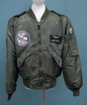 Image of 2017.008.030.3 - Moffett Field B-17 Jacket, 2006. Green nylon flight jacket. The material has a satin finish. Cuffs, collar, and the bottom of the jacket are made of an elastic polyester material. The jacket has two shoulder straps extending from the top of the sleeve to button near the collar. Along the waist are two pockets with snap button closures. On the front at the bottom of the jacket is a flap of fabric that folds over the bottom of the zipper and is secured with a snap button closure. On the proper right chest is a large, round patch: embroidered in the front is a gray B-17 plane with red detailing on the wings. On the proper left chest, .5 inches from the zipper is a patch sewn on three sides with an opening facing the zipper. Also on the proper left chest, is a Velcro, leather name tag with silver etched lettering and a illustration of pilots wings with a shield in the middle. In the proper right hand shoulder, is a blue round patch featuring a gold embroidered image: two circles vertically stacked, the top circle is smaller than the bottom; inside the bottom circle is a white star with a red circle in the middle. Gold wings emerge from the sides of the bottom circle and point straight up. Below the patch, is a arm pocket with a gold-colored metal circle. On top of this pocket are four pen pockets. On the back of the jacket is a large embroidered image of a gray B-17 with red detailing on the wings. The B-17 is flying in front of the two grayish clouds, the propellers are made to appear as if they are spinning.